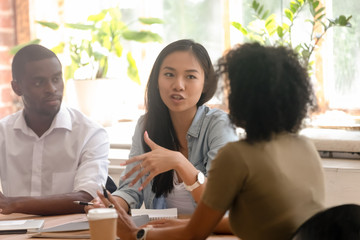 Asian female worker speaking telling opinion talking to african colleagues