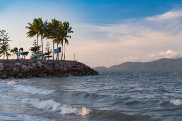 Blick aufs Meer mit steinigem Küstenabschnitt und Palmen