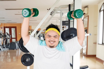 Happy fat man lifts dumbbells in gym center