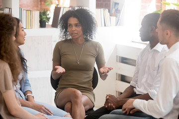 African woman speaking at diverse team training or group therapy