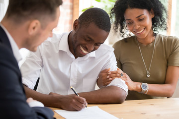Happy african family couple customers sign mortgage loan insurance contract