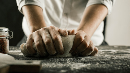 Male chef hands knead dough with flour on kitchen table