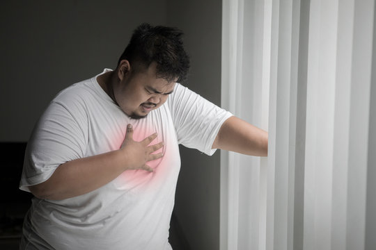 Obese man having a heart attack near the window