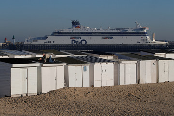 A man works on the roof of a beach cabin as the Spirit of Britain, a ferry with the trans-Channel ferry company P&0, arrives in the harbour of Calais