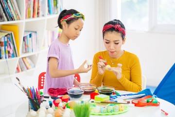 Young mother teaches her daughter to paint eggs