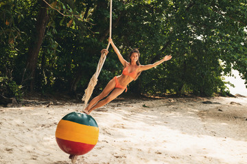 Happy woman on swings made from old buoy on the beach