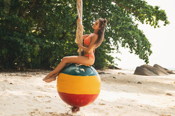 Happy woman sitting on swings made from old buoy
