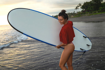 Young and sexy woman with a longboard during surfing session on the beach