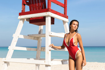 Sexy woman in red swimsuit posing beside a lifeguard tower
