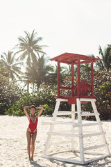 Sexy woman in red swimsuit beside lifeguard tower on the beach