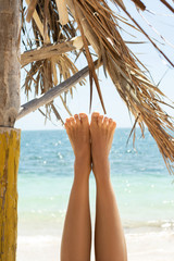 Female feet against background of the beautiful blue sea