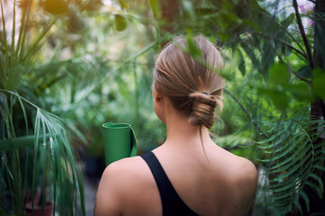 Portrait of cute young woman holding a rolled yoga mat in jungle. Sunny day. Back view