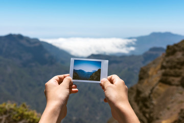 Young girl holding instant photo of the Teneguia volcano. La Palma, Canary islands, Spain. Concept holiday, tourist on vacation background.
