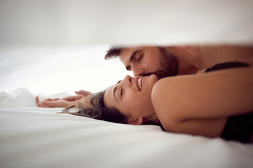 Passionate couple is lying in bed together. Enjoying the company of each other..