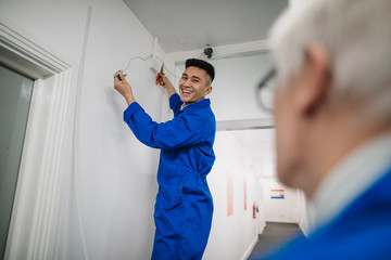 Trainee Electrician Fitting a Security Camera