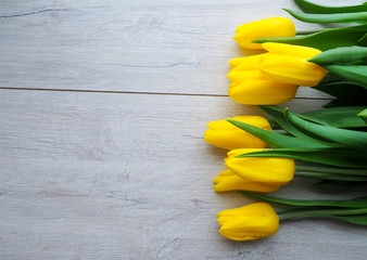 Yellow tulips on wooden background copy space