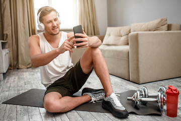 Young well-built man go in for sports in apartment. Happy positive guy sit on carimate on floor and take selfie. Dumbbells and water bottle beside.