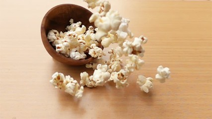 Fototapete - Popcorn fall on the top of a wooden table in Slow Motion