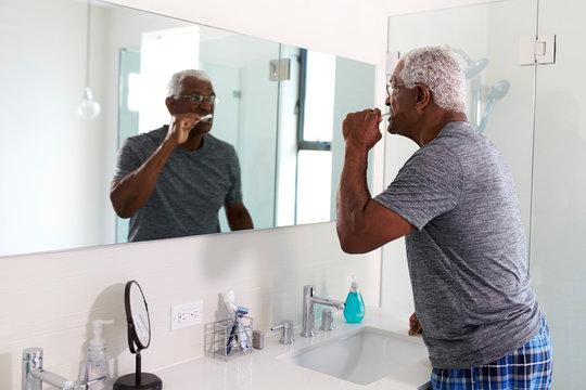 Senior Man Looking At Reflection In Bathroom Mirror Wearing Pajamas Brushing Teeth