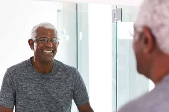 Smiling Senior Man Looking At Reflection In Bathroom Mirror Wearing Pajamas