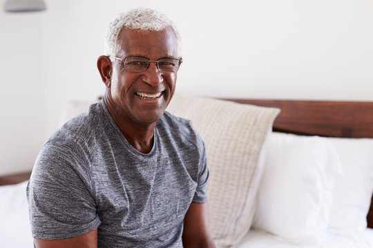 Portrait Of Smiling Senior Man Sitting On Side Of Bed At Home Looking Positive