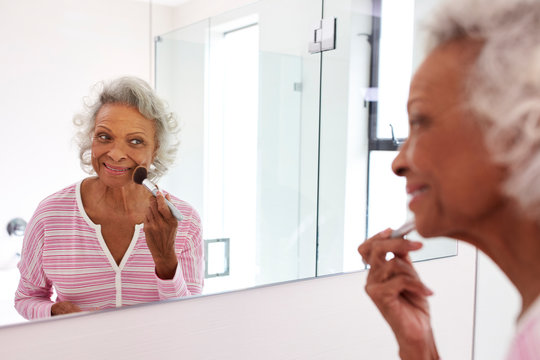 Senior Woman Looking At Reflection In Bathroom Mirror Putting On Make Up
