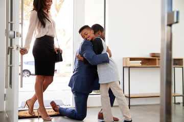 Son Greeting And Hugging Working Parents As They Return Home From Work