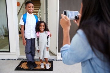Mother Taking Photo Of Children With Cell Phone On First Day Back At School