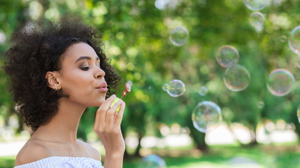 Portrait of young beautiful woman making soap bubbles