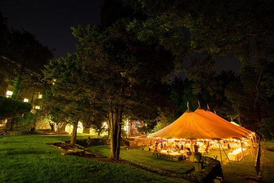 a wedding tent at night surrounded by trees with an orange glow from the lights. - wedding tent series