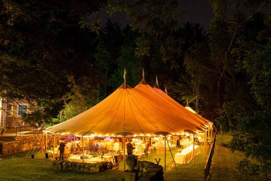 a wedding tent at night surrounded by trees with an orange glow from the lights, long exposure - wedding tent series