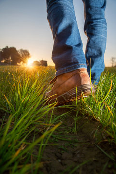a walks farmer's work shoes in his field towards his tractor