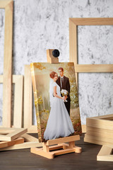 Wedding photo printed on canvas, a wooden easel and stretcher bars on table