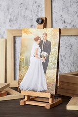 Canvas print: wedding photography on a wooden easel and stretcher bars on table