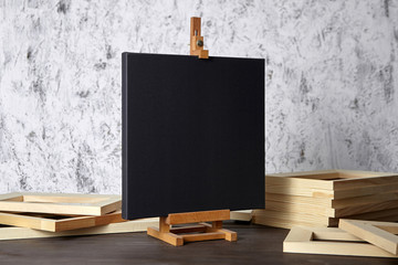 Black blank cotton canvas for acrylic and oil paints, a wooden easel and stretcher bars on table