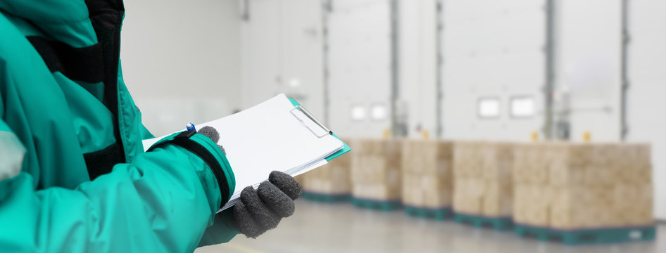 Hand of worker with clipboard checking goods in freezing room or warehouse. Export-Import Logistics system concept. Banners with copy space