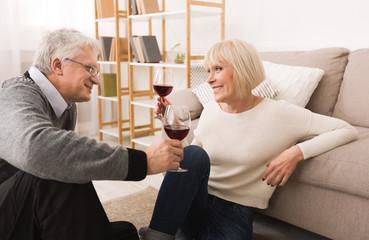 Loving senior couple enjoying wine at home