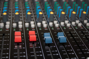 Studio mixing desk close up showing a red and blue fader