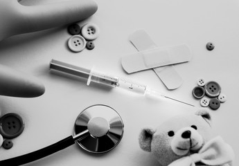 Vaccinating children concept, syringe stethoscope, teddy bear toy, buttons, flat lay monochrome view.