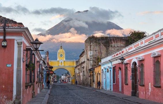 Colonial Architecture and Street Scene during Early Morning Sunrise in Antigua Guatemala with Santa Catalina Arch and Agua Volcano in the Background