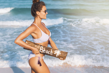 Sexy woman wearing swimsuit with old wooden billboard on the beach