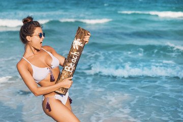 Sexy woman wearing swimsuit with old wooden sign n the beach