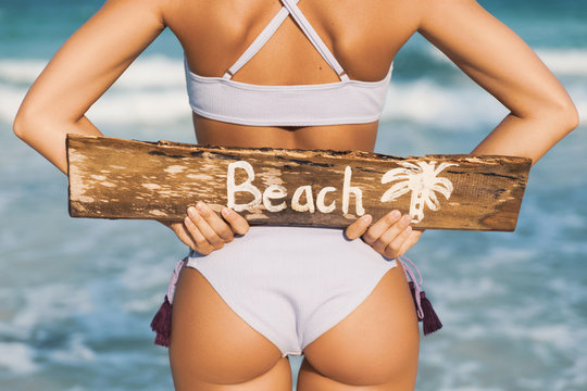 Sexy woman wearing swimsuit with old wooden sign on the beach