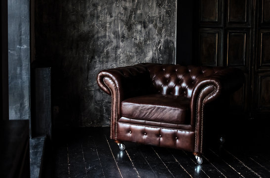 Sofa of brown leather standing in center