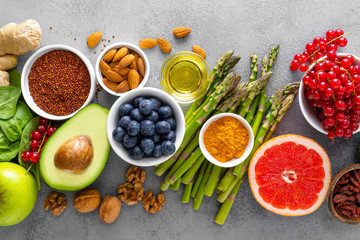 Healthy food background, spinach, quinoa, apple, blueberry, asparagus, turmeric, red currant, broccoli, mung bean, walnuts, grapefruit, ginger, avocado, almond, green peas and goji, top view