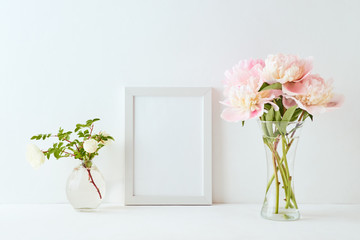 Mockup with a white frame and pink peonies in a vase on a white background