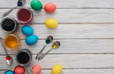 Colorful easter eggs  on wooden background.On a white wood table colored eggs,paint,spoons.Happy religious day,traditional for people. Top view.Copy space.