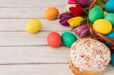 Colorful easter eggs,cake,spring tulips  on wooden texture background.On a white wood table,colored eggs,flowers,bread.Happy religious day,traditional for people. Top view.Copy space.