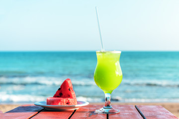 a glass of fresh green tropical fruit juice on the beach, and a plate with watermelon on the table, against the sea. The concept of summer holidays and vacation