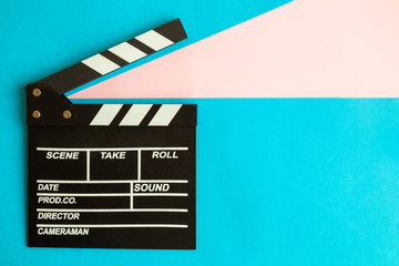 Flat lay of clapperboard against blue background.